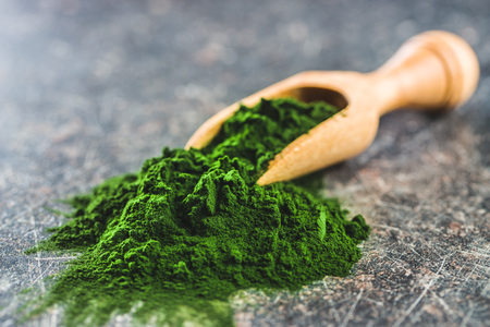 Green chlorella powder in wooden scoop. Imagens
