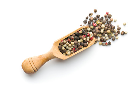 Different types of dried peppercorn in scoop isolated on white background.