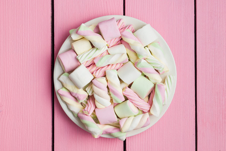 Sweet colorful marshmallows on pink table. Top view.