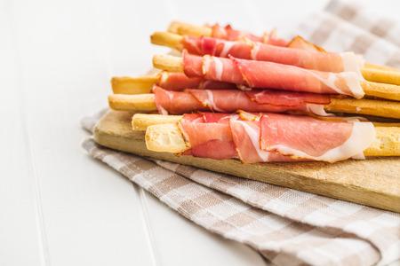 Parma ham prosciutto with grissini breadsticks on cutting board.