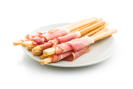 Parma ham prosciutto with grissini breadsticks on plate isolated on white background.