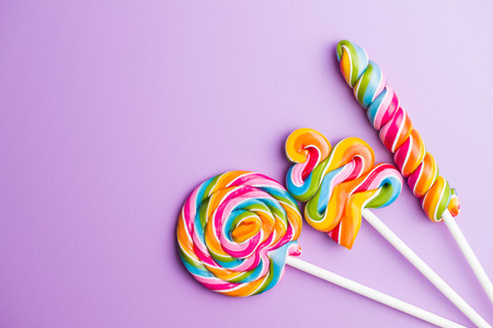 Various colorful lollipops on violet background.