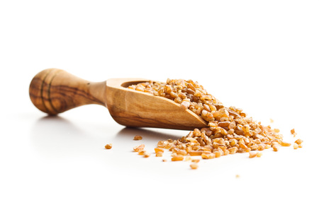 Dry bulgur wheat grains in wooden scoop isolated on white background. Reklamní fotografie