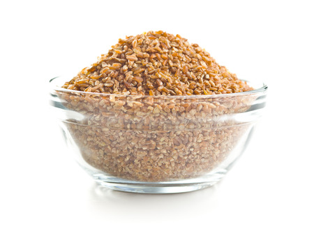 Dry bulgur wheat grains in bowl isolated on white background.