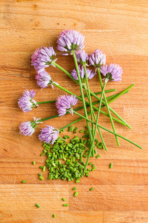 Chopped chives with Flowers on old kitchen table.