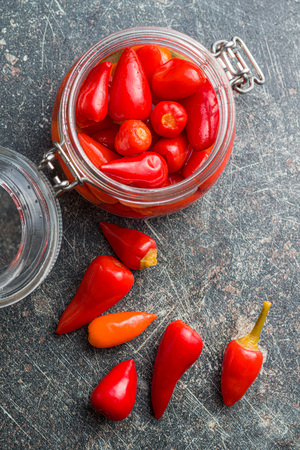 Pickled chili peppers on old kitchen table. Banco de Imagens