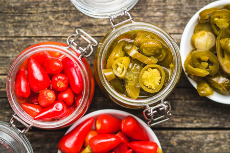 Pickled chili peppers and jalapeno peppers in jar. Banco de Imagens