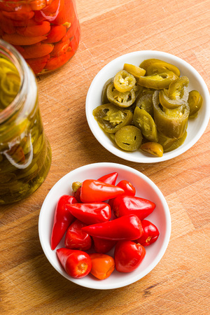 Pickled chili peppers and jalapeno peppers in bowl.