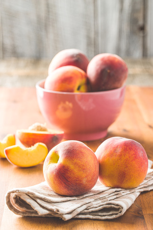 Sweet peaches fruit on wooden table.