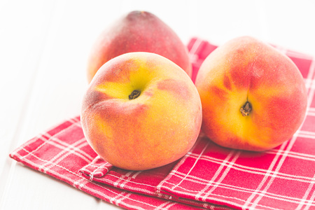 Sweet peaches fruit on checkered napkin. Banco de Imagens