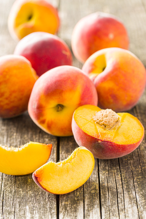 Sweet peaches fruit on old wooden table.