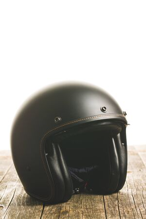 Vintage open face motorcycle helmet on wooden table.