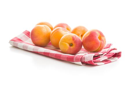 Sweet apricot fruits on checkered napkin isolated on white background. Banco de Imagens