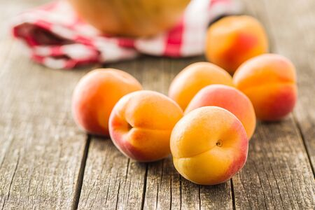 Sweet apricot fruits on old wooden table.