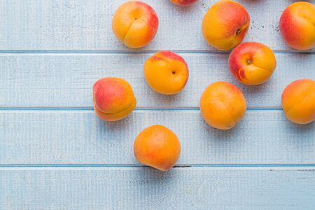 Sweet apricot fruits on blue wooden table. Top view.