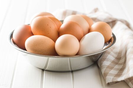 Raw chicken eggs in bowl.