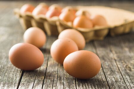Raw chicken eggs on old wooden table.