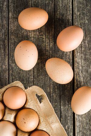 Raw chicken eggs on old wooden table. Top view. Banco de Imagens