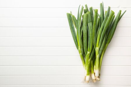 Green spring onions on white table. Top view.