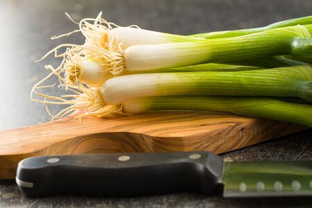 Green spring onions on wooden cutting board.