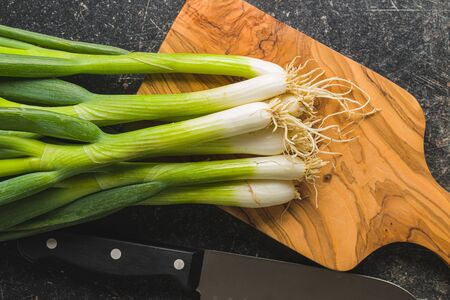 Green spring onions on wooden cutting board. Top view. Banco de Imagens