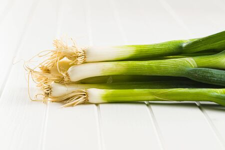 Green spring onions on white table. Banco de Imagens