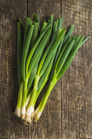Green spring onions on old wooden table. Top view. Banco de Imagens