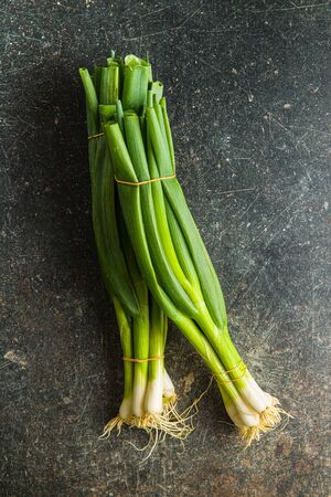 Green spring onions on old kitchen table. Top view.