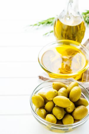 Green olives and olive oil in glass bowl on white table.