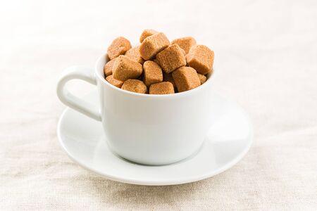 Brown sugar cubes in coffee mug. Archivio Fotografico