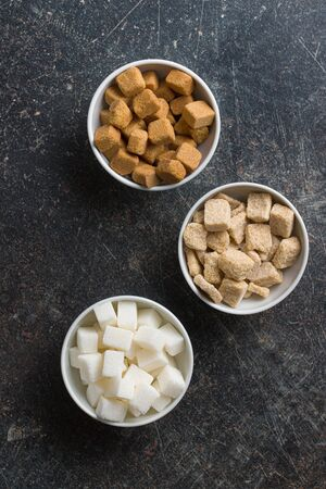 White and brown sugar cubes in bowls. Top view.