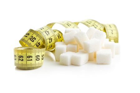 Sweet white sugar cubes and measuring tape isolated on white background. Stock Photo