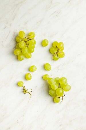 Tasty green grapes. White grape on white table. Top view. Stock Photo