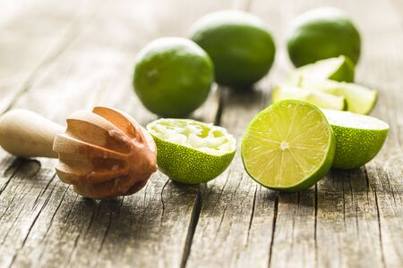 Wooden citrus squeezer and green lime on wooden table.