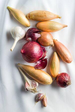 The golden shallot onion and garlic. Fresh bulbs on tablecloth. Top view. 版權商用圖片