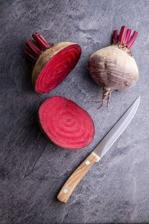 Tasty raw beetroot. Sliced beetroot and knife on kitchen table. Top view.