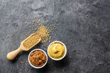 Yellow mustard and whole grain mustard and mustard seeds on kitchen table. Top view. Reklamní fotografie