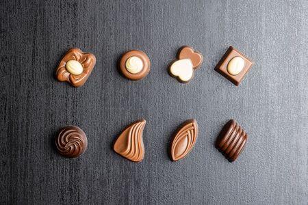 Various chocolate pralines on black table. Top view.
