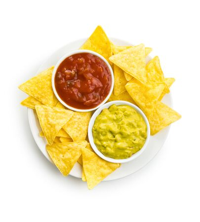 Corn nacho chips with avocado and tomato dip. Yellow tortilla chips and guacamole isolated on white background.