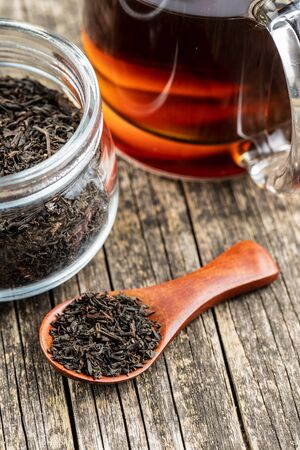 Dried black tea leaves in wooden spoon. Stock Photo