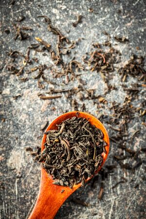 Dried black tea leaves in wooden spoon. Top view. Stock Photo