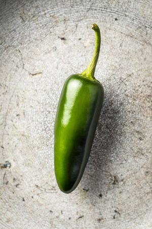 Green jalapeno pepper on old kitchen table. Top view.