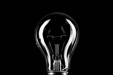 Classic light bulb on black background.