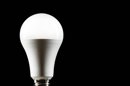 Energy saving light bulb on black background. LED light bulb.