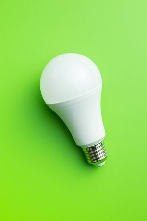 Energy saving light bulb on green background. LED light bulb. Top view.