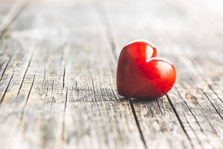 Rood hart op oude houten tafel. Liefde hart. Stockfoto