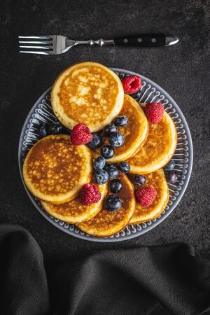 Sweet homemade pancakes with blueberries and raspberries on old kitchen table. Archivio Fotografico - 139977544