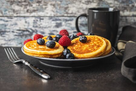 Sweet homemade pancakes with blueberries and raspberries on old kitchen table. Archivio Fotografico - 139887649