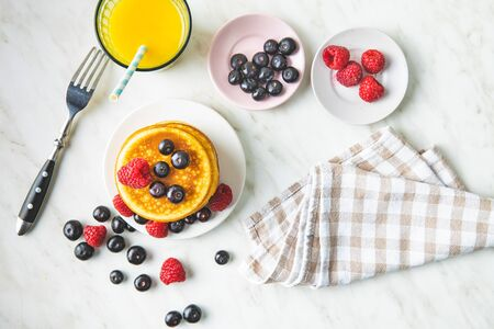 Sweet homemade pancakes with blueberries and raspberries. Tasty breakfast with juice. Top view. Archivio Fotografico - 139978826