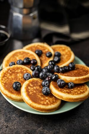 Sweet homemade pancakes and blueberries on old kitchen table. Archivio Fotografico - 139978802